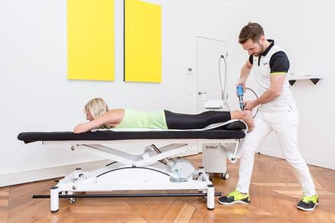 Séances de kinésithérapie avec un kiné spécialistes du sport et une patiente qui fait des ondes de choc