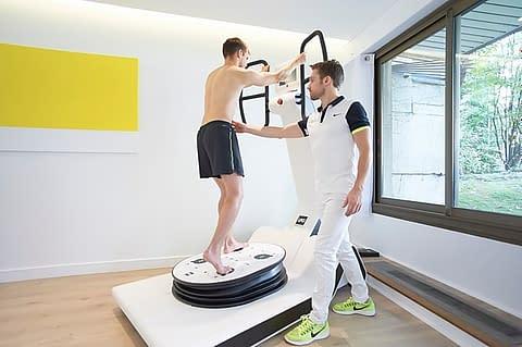 Cabinet de kinésithérapie à Paris, avec un kinésithérapeute et ostéopathe et son patient pour un bilan de kinesitherapie et un séance de rééducation sur le Huber 360 LPG