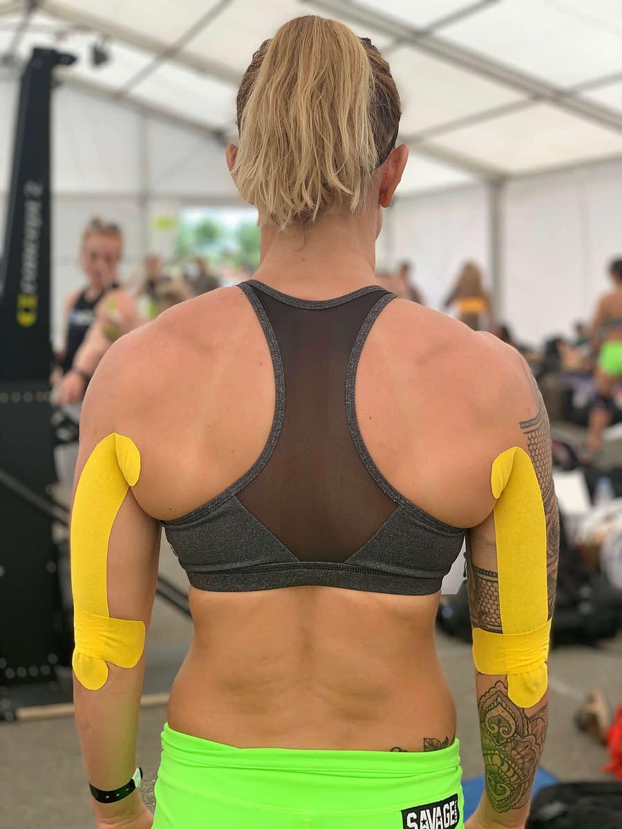 Femme de dos portant des K-tapes au niveau des épaules