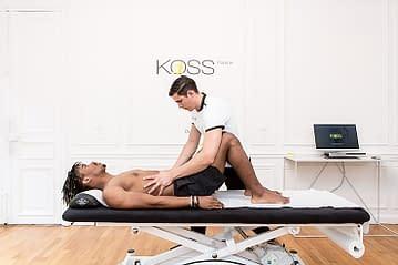 Intérieur du cabinet kiné KOSS Paris avec un coach et un patient en séance de rééducation urgence Kine paris