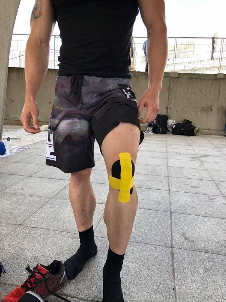 Homme debout portant une K-tape sur le genou avant le sport